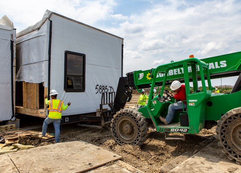 Forklift moving modular building module into place
