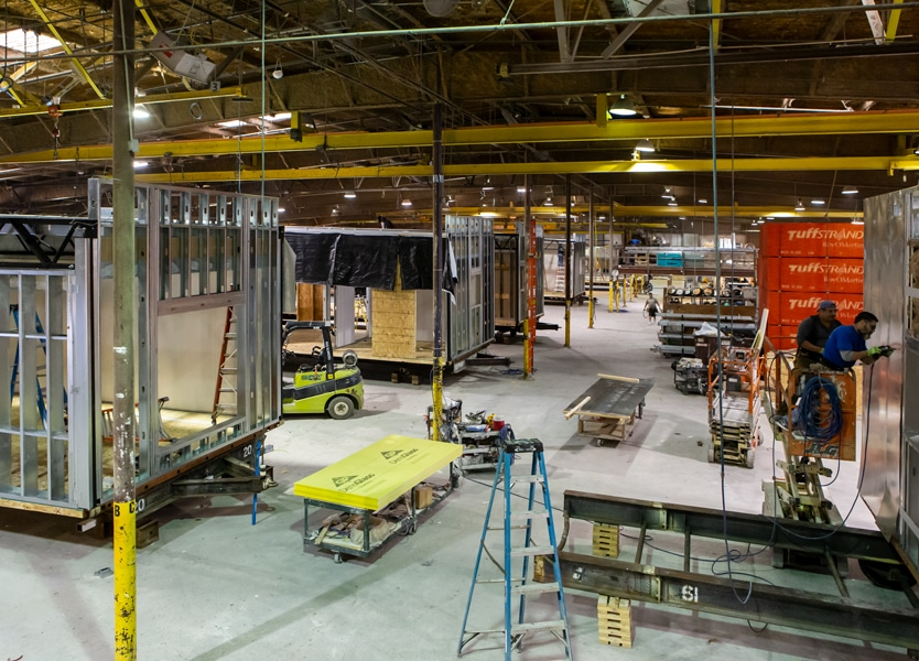 Modular construction plant interior with various stages of module completion on the assembly line